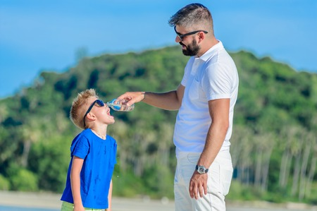 Portrait of father giving water to his thirsty handsome boy on the desert tropical beach
