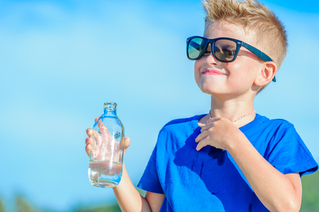 Portrait of a thirsty handsome boy in sunglasses drinking water on the desert tropical beach Stock Photo
