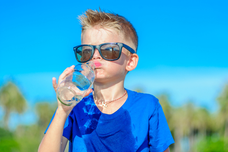 Portrait of a thirsty handsome boy in sunglasses drinking water on the desert tropical beach Zdjęcie Seryjne