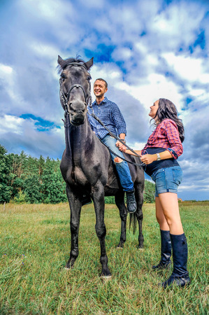 he: Awaiting the child, walking on the meadow. Young couple - she is a handsome brunette with long hair, pregnant; he is tall and brave, astride a black horse. Stock Photo