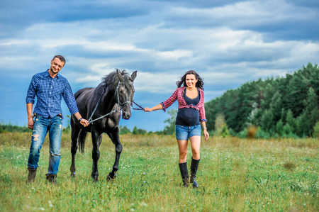 move in: Awaiting the child, walking on the meadow. Young couple - she is a handsome brunette with long hair, pregnant; he is tall and brave, astride a black horse. Stock Photo