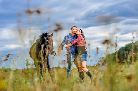 View through the grass: young couple - she is handsome brunette with long hair, pregnant; he is tall and brave, holding the reins of the black horse, a walk on the meadow. Wonderful sky behind them Stock Photo