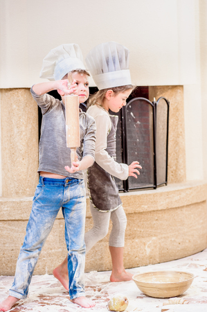 whiff: Two siblings - boy and girl - in chefs hats near the fireplace sitting on the kitchen floor soiled with flour, playing with food, making mess and having fun