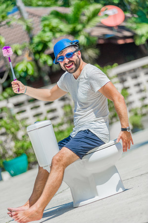 The bearded man in goggles astride the toilet, which is installed in the middle of the street. Toilet brush in his hand, cooking pan on his head