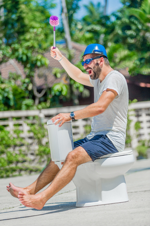 a toilet stool: The bearded man in goggles astride the toilet, which is installed in the middle of the street. Toilet brush in his hand, cooking pan on his head