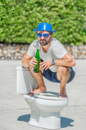 a toilet stool: The bearded man in goggles astride the toilet, which is installed in the middle of the street. Toilet brush in his hand, cooking pan on his head. Drinking beer