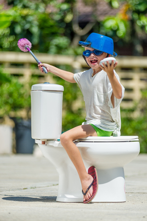 Absurd picture: cute boy in goggles sitting on the toilet, which is installed in the middle of the street. Pan on his head