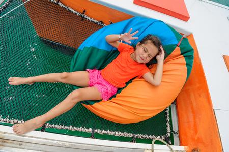 Cute girl at chair-bag on catamarans hammock Stock Photo