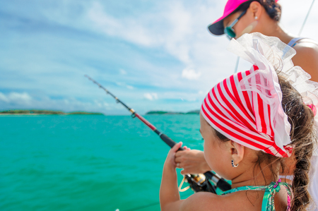 A girl and her mom fishing on a boat. Colorful tropical pattern around. Stock Photo