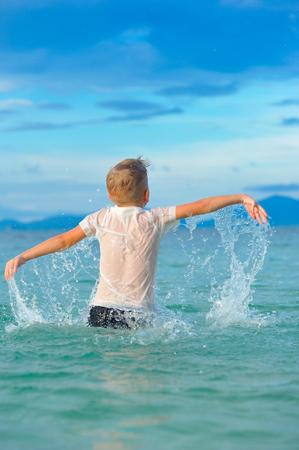 Alsof een vogel: een close-up portret van een knappe jongen in een nat slimfit overhemd springt en fladdert over het water, veel spatten en plezier Stockfoto