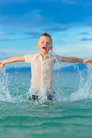 Als ob ein Vogel: ein Nahaufnahmen Porträt eines hübschen Jungen in nassen, schlanken Fithemden springt und flattert über das Wasser, viele Spritzer und Spaß