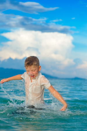 As if a bird: a close-up portrait of a handsome boy in wet slim fit shirt jumps and flutters over the water, a lot of splashes and fun Stock Photo