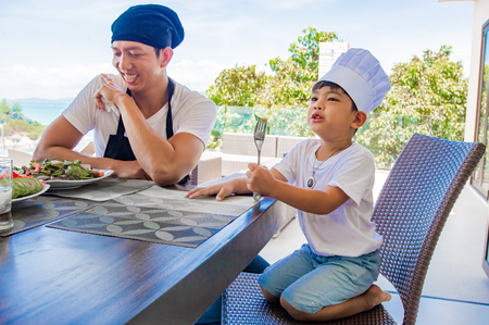 Thai man and his cute son having lunch at home. Playing game of cooks: apron, chefs hat and thai food. Stunning seaview luxury villa