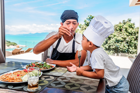 Thai man and his cute son having lunch at home. Playing game of cooks: apron, chefs hat and thai food. Stunning seaview luxury villa. Vibrant color concept Stock Photo