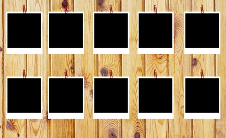 set of ten old blank polaroids frames lying on a wood surface  photo
