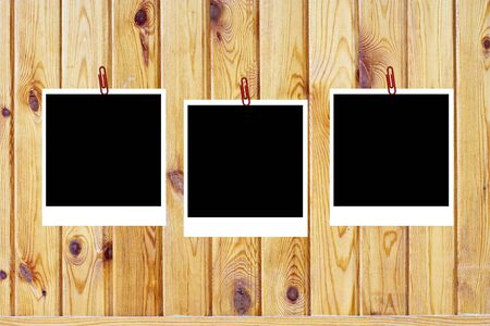 set of three old blank polaroids frames lying on a wood surface  photo