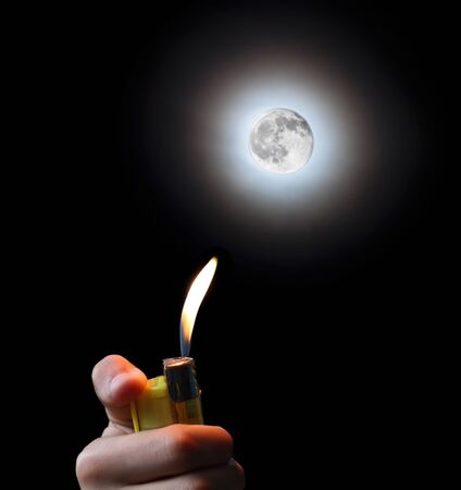 hand with a cigarette lighter and the moon photo