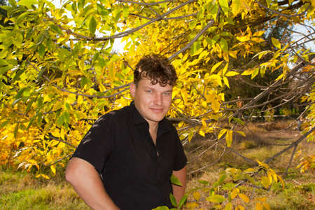 suave: man in a black shirt on the background of autumn