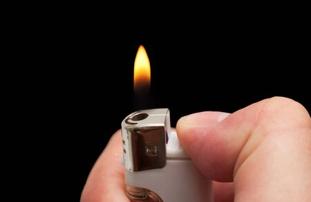 hand with a cigarette lighter on a black background photo