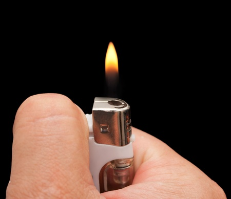 hand with a cigarette lighter on a black background Stock Photo - 12997635