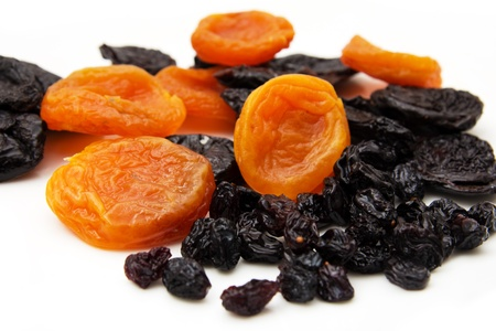 dried apricots, prunes and raisins on a white background