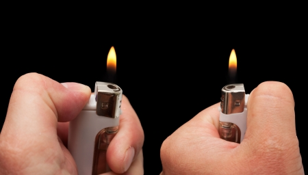 hand with a cigarette lighter on a black background Stock Photo - 14570876
