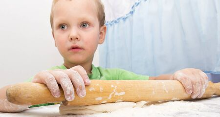 3 persons only: boy rolls the dough Stock Photo