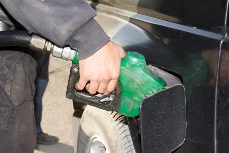 мужская рука заправки автомобиля топливом на автозаправочной станции Фото со стока