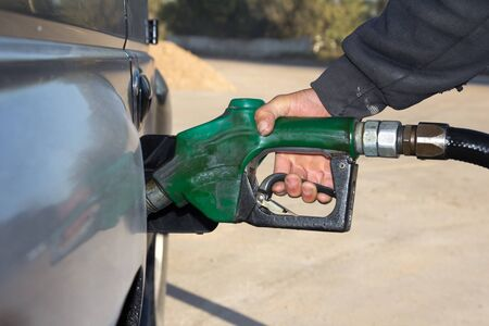 refilling: male hand refilling the car with fuel on a filling station
