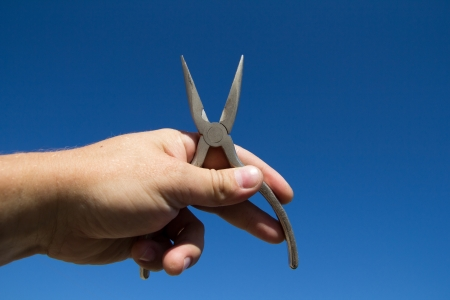 Pliers in hand man on a background of blue sky photo