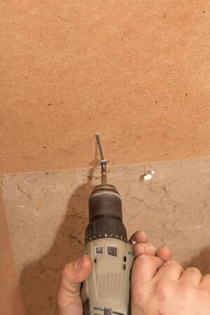 tightening the screws into the wood wall Stock Photo - 17366017