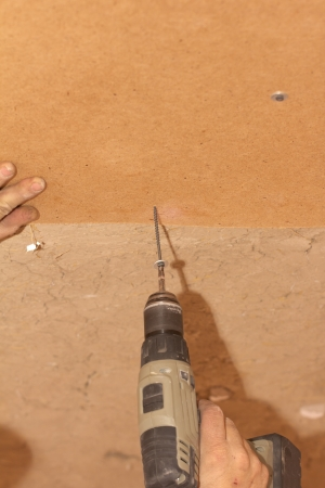 tightening the screws into the wood wall Stock Photo - 17366063