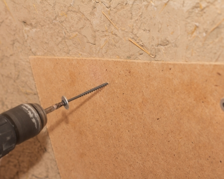 tightening the screws into the wood wall Stock Photo - 17365876