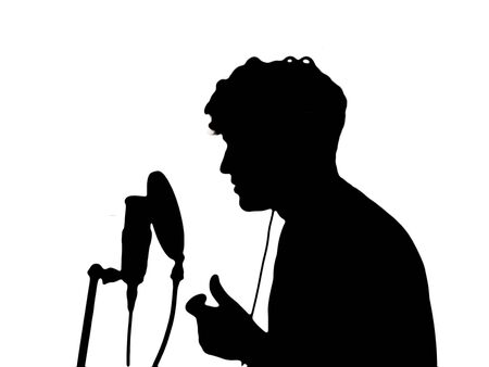 man in headphones singing into a microphone on a white background photo