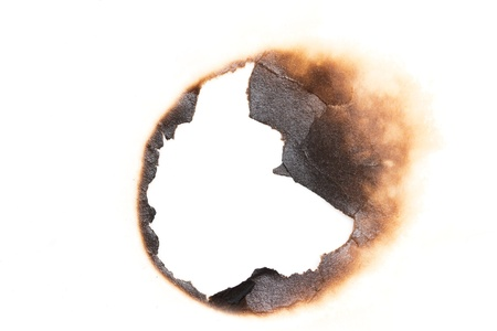 scorch: burned hole on a white paper background