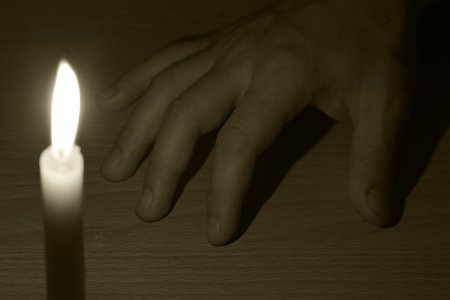 votive: dead hand and the light from the candles Stock Photo