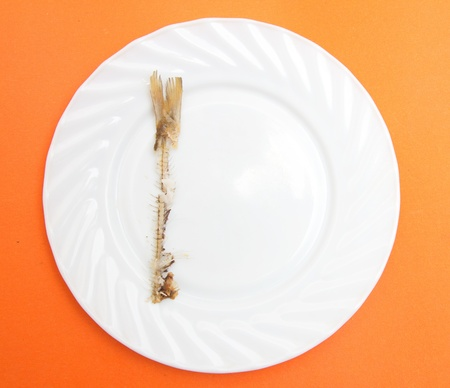 skeleton of fried fish on a plate on the orange background Stock Photo - 18892705