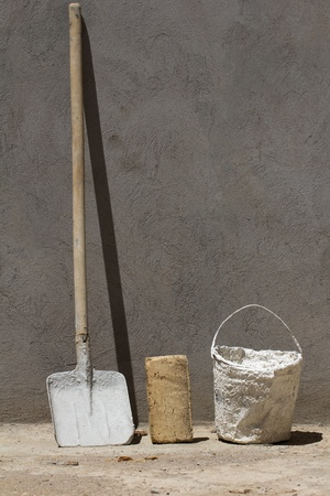 bucket and spade on a background of brick and concrete wall photo