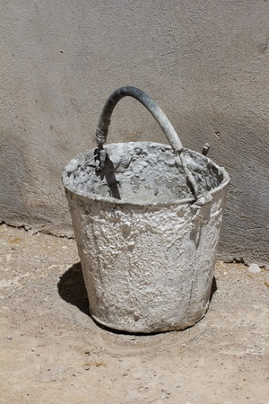 thirstiness: bucket against the concrete wall Stock Photo