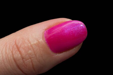 covered with red fingernail polish on a black background. macro photo