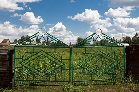 iron fence and a blue sky with clouds photo