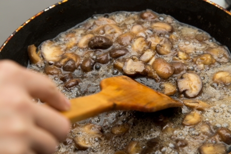 champignon mushrooms fried in a pan photo