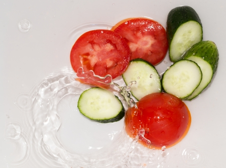 cucumber and tomato in water on white background photo