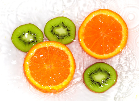 squelch: orange and kiwi in water white Stock Photo