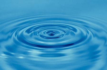 circulos concentricos: una gota de agua cae en el azul. macro ...