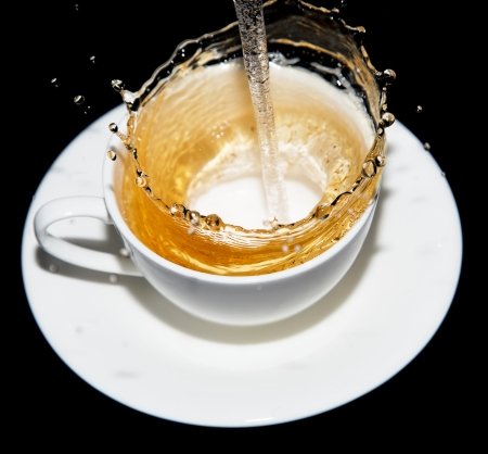 tea being poured into a saucer with splashes on a black background photo