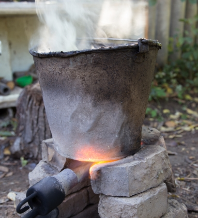 heats: flame from a gas burner heats the bucket Stock Photo