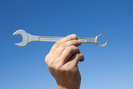 Hand with a wrench on a background of the sparkling sky. photo