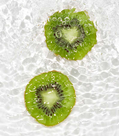 juicy kiwi fruit in water on a white background. macro photo