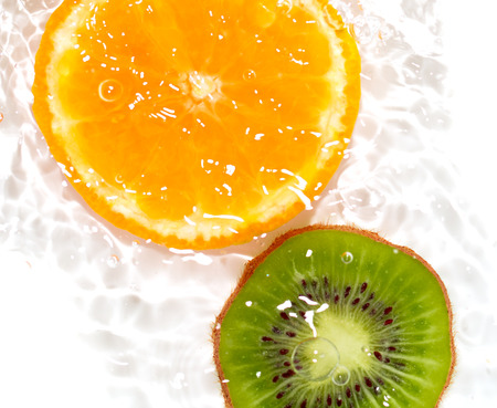 squelch: juicy kiwi and orange in water on a white background. macro